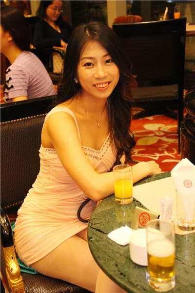 Beautiful Asian woman sitting and leaning on a table, smiling.